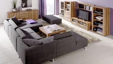 Sofa de esquina modular en color gris oscuro combinado con muebles de madera natural
