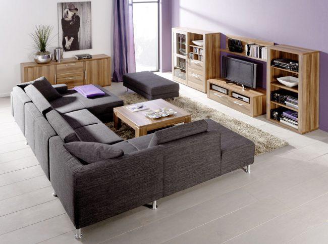 Sofa-de-esquina-modular-en-color-gris-oscuro-combinado-con-muebles-de-madera-natural